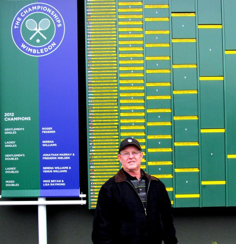 Des in front of the board displaying the previous year's winners