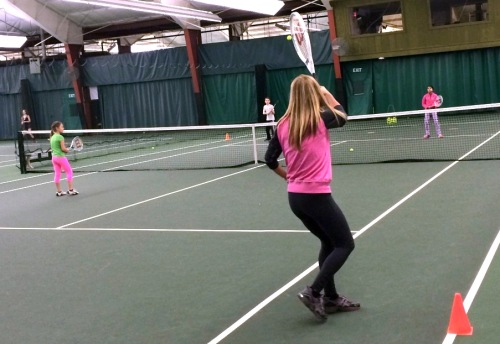 Ginny Purdy playing a forehand with daughter Chloe at the net